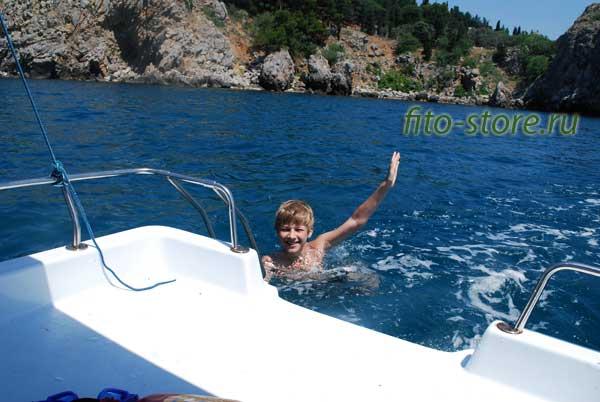 Счастливый ребенок купается в море